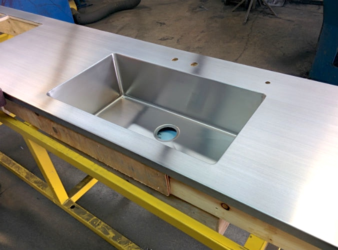 Stainless steel counter with integrated sink